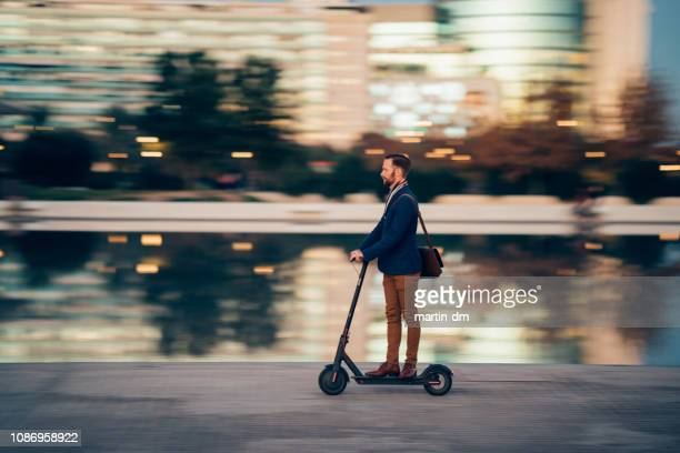 businessman riding a scooter in the city - city stock pictures, royalty-free photos & images