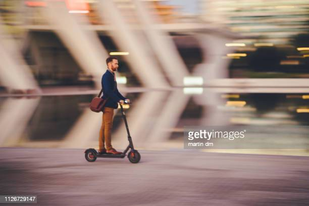 businessman riding a scooter in the city - electric scooter stock pictures, royalty-free photos & images