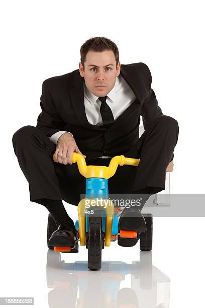 businessman riding a tricycle - tricycle stock pictures, royalty-free photos & images