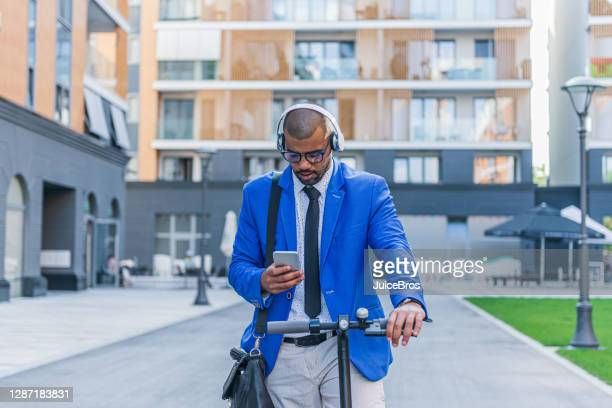 businessman riding an electric scooter in the city - alternative lifestyle stock pictures, royalty-free photos & images