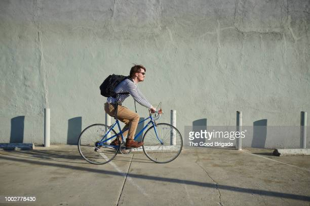 businessman riding bicycle along concrete wall - radfahren stock-fotos und bilder