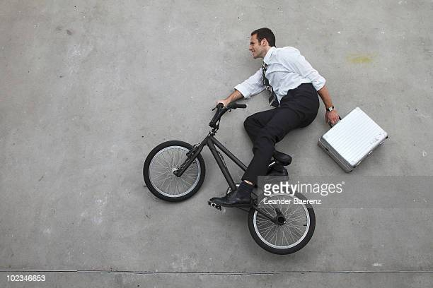 Businessman with briefcase riding bicycle