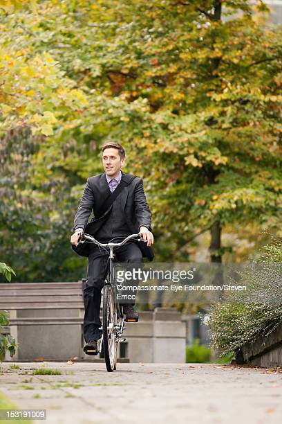 Businessman riding bicycle in park