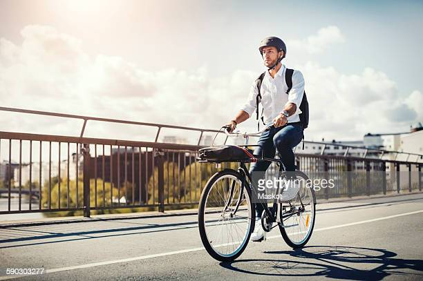 Businessman riding bicycle on bridge against sky