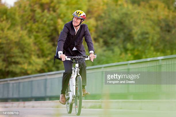 Businessman riding bicycle on bridge
