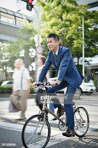 Businessman riding bicycle on crossroad