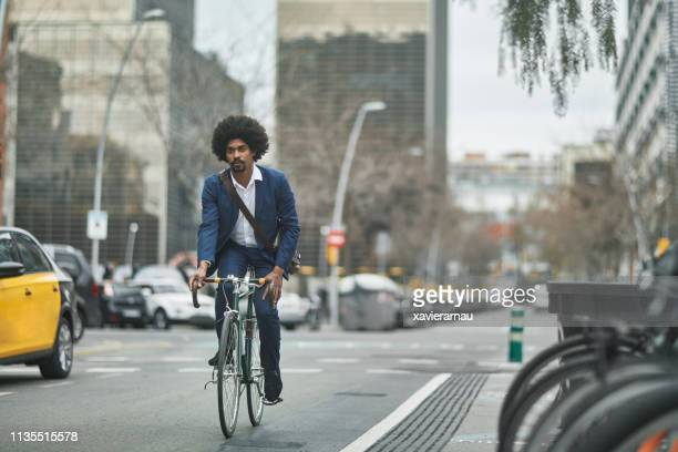 businessman riding bicycle on street in city - afro caribbean ethnicity stock pictures, royalty-free photos & images