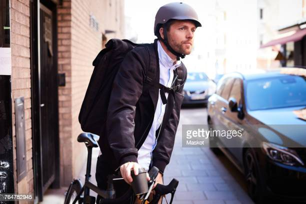 Businessman riding bicycle on street in city