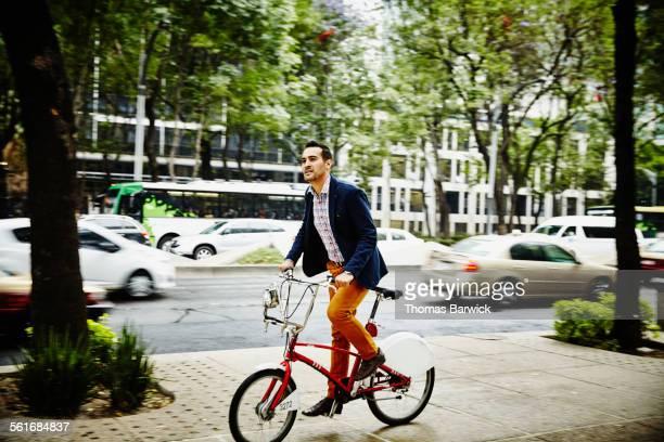 Businessman riding bike on city sidewalk