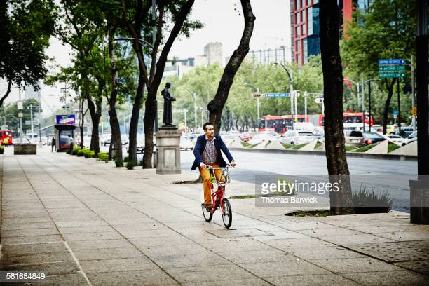 businessman riding bike on sidewalk in city - characteristic of mexico photos et images de collection