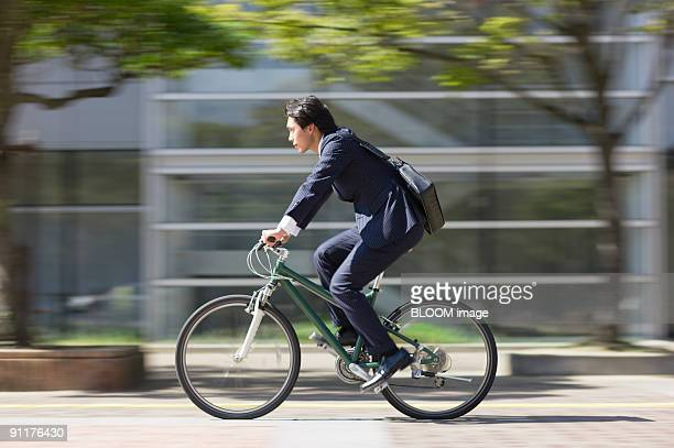 businessman riding bike, side view - japan commuters ストックフォトと画像