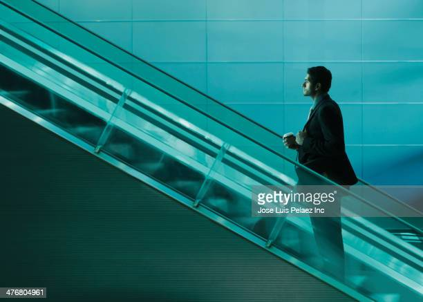 Businessman riding escalator