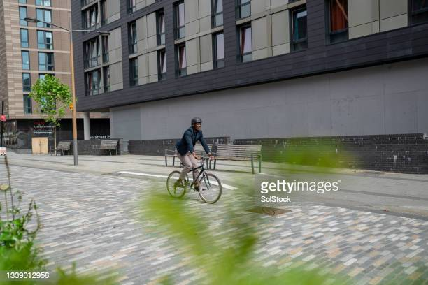 businessman riding his bicycle in the city - green blazer stock pictures, royalty-free photos & images