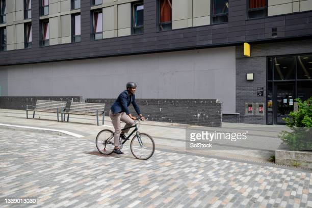 businessman riding his bicycle to work in the city - green blazer stock pictures, royalty-free photos & images
