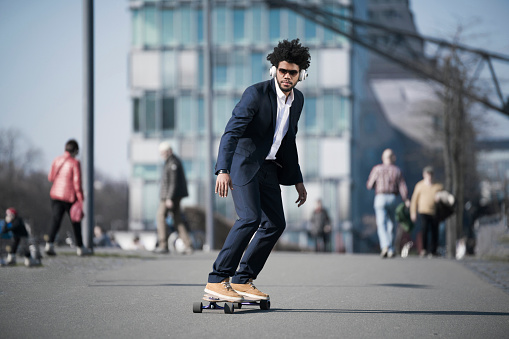 Businessman riding longboard in front of skyscraper - gettyimageskorea