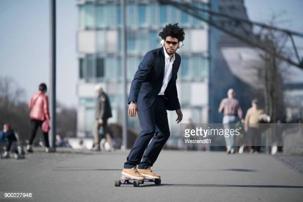 Businessman riding longboard in front of skyscraper