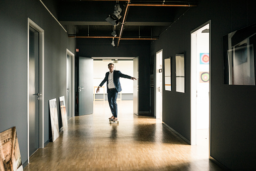 Businessman riding longboard on office floor - gettyimageskorea