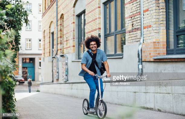 Businessman riding push scooter in city