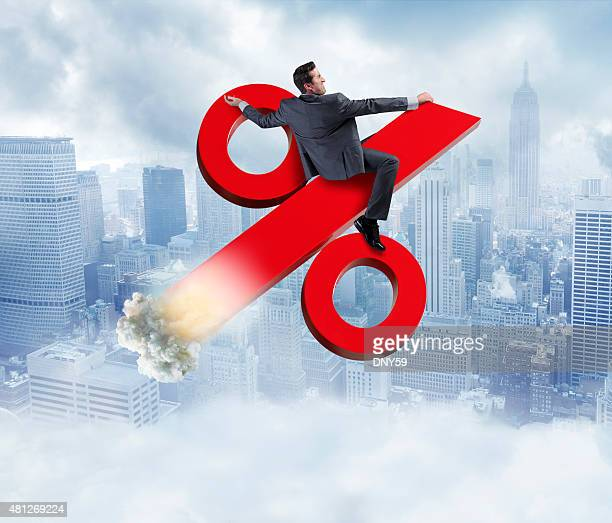 businessman riding rising percentage sign - interest rate stock pictures, royalty-free photos & images