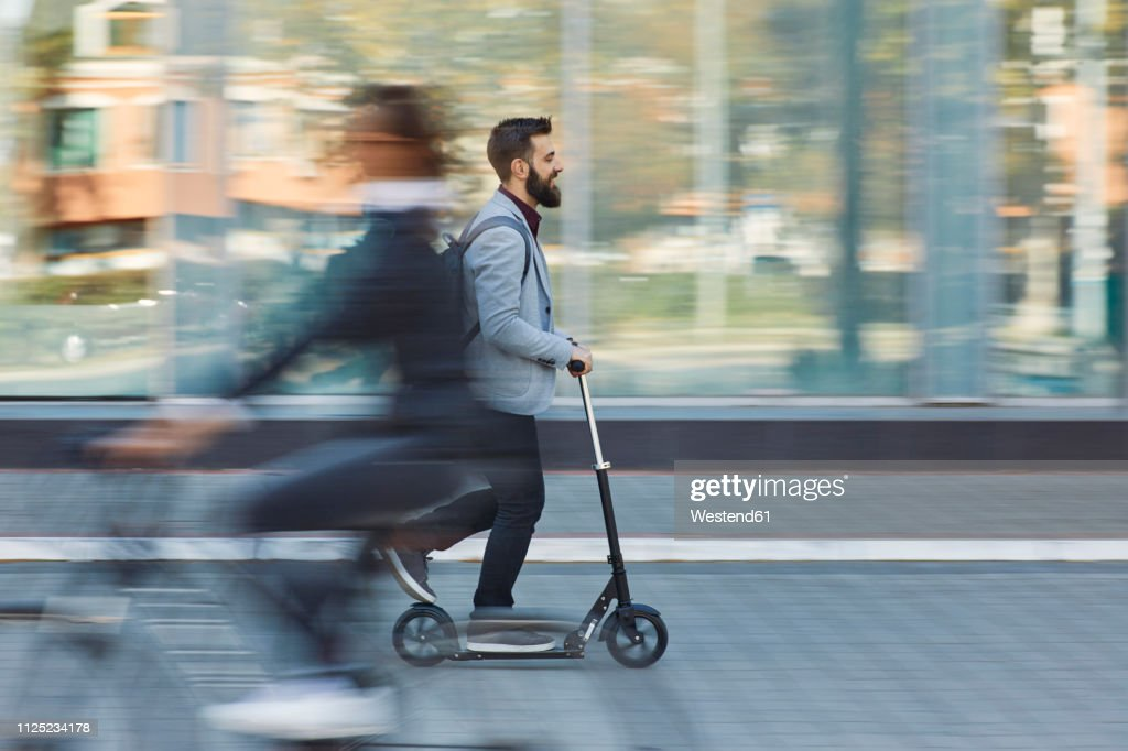 Businessman riding scooter along office building : Stock Photo