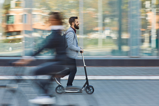 Businessman riding scooter along office building - gettyimageskorea