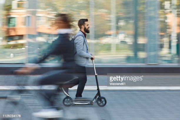 businessman riding scooter along office building - bewegung stock-fotos und bilder