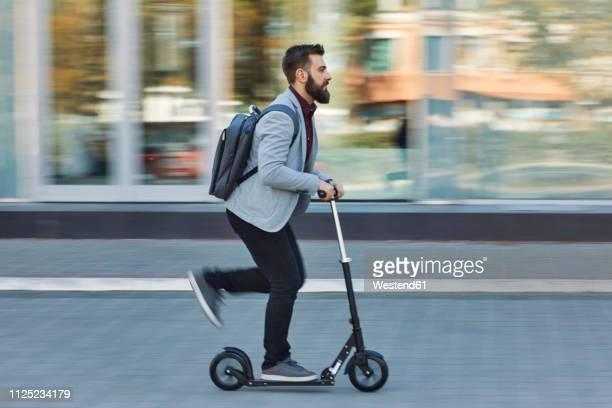 businessman riding scooter along office building - motor scooter stock pictures, royalty-free photos & images