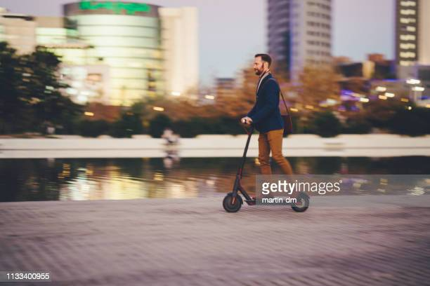 businessman riding scooter in spain - electric scooter stock pictures, royalty-free photos & images