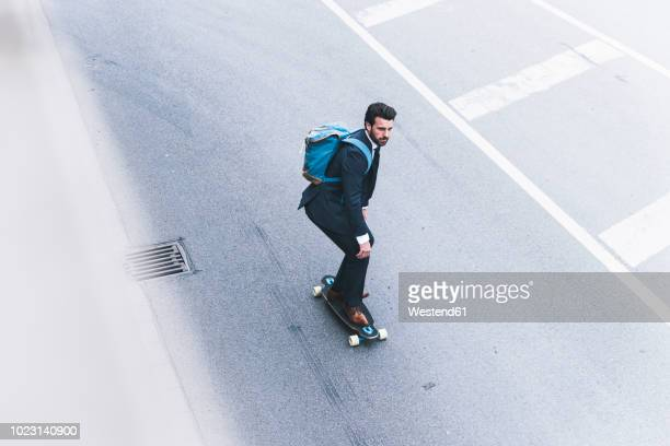 businessman riding skateboard on the street - unabhängigkeit stock-fotos und bilder