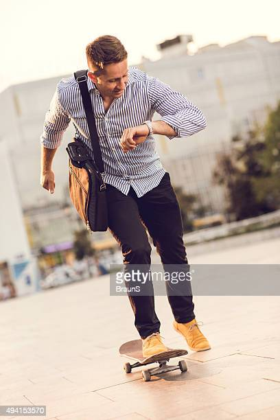 Businessman riding skateboard while checking the time on his watch.