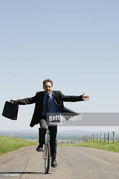 Businessman riding unicycle II