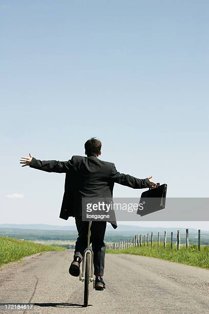 Businessman riding unicycle III