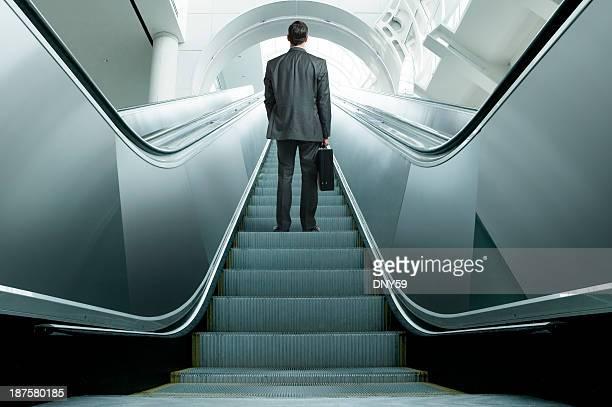 Businessman riding up an escalator
