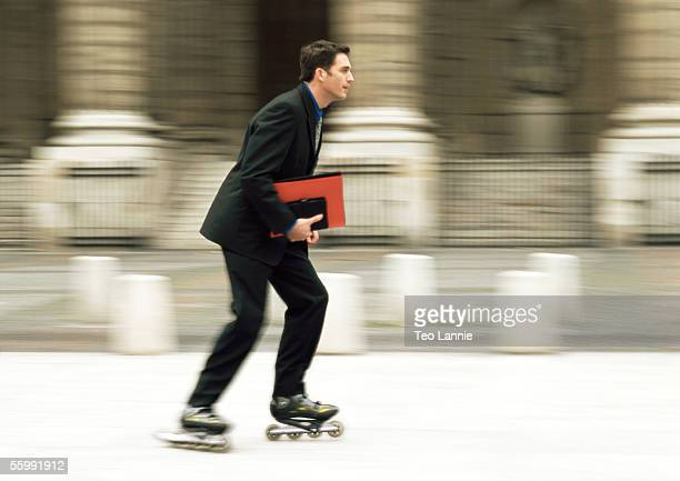 Businessman rollerblading in front of building, blurred.