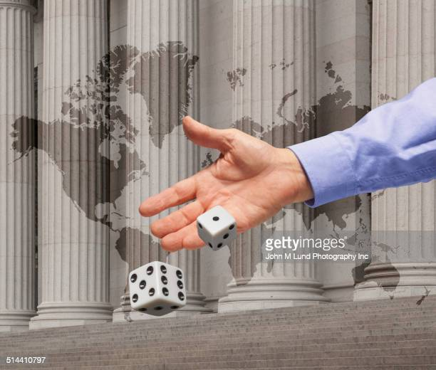 Businessman rolling dice by building with world map
