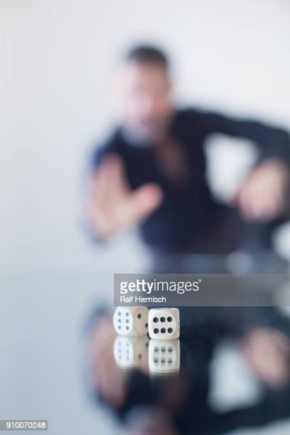 Businessman rolling dice on glass table
