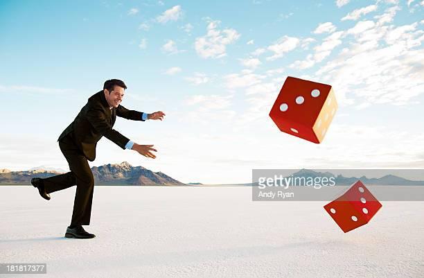Businessman rolling giant dice on salt flats.