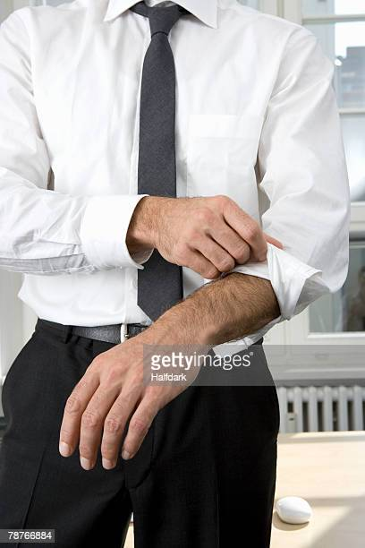 A businessman rolling up his sleeves