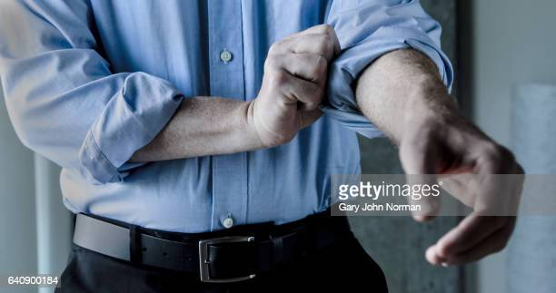 businessman rolling up shirt sleeve. - rolled up stock pictures, royalty-free photos & images