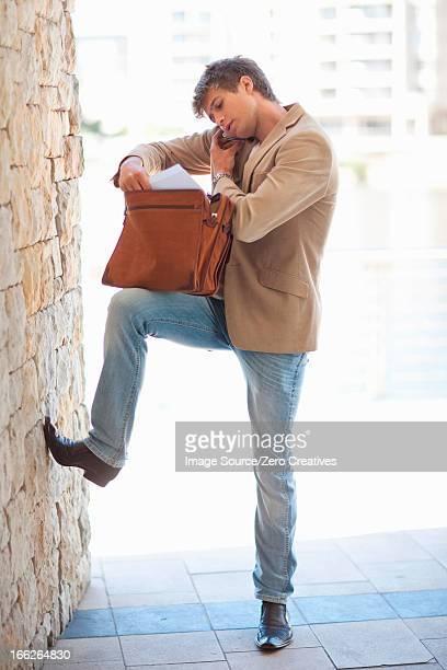 Businessman rooting through briefcase
