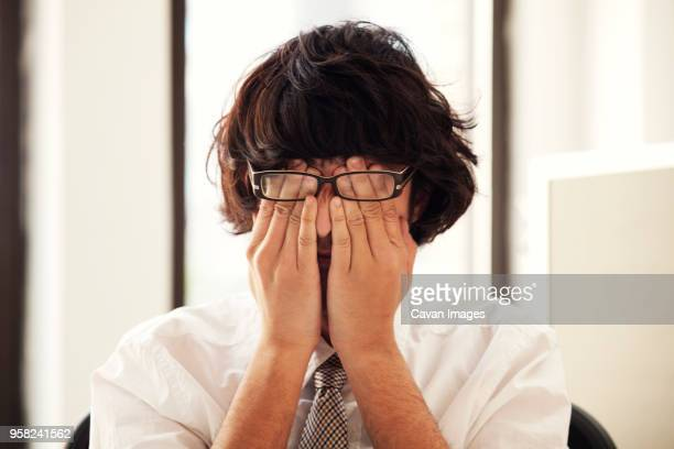 Businessman rubbing eyes while sitting on chair in office