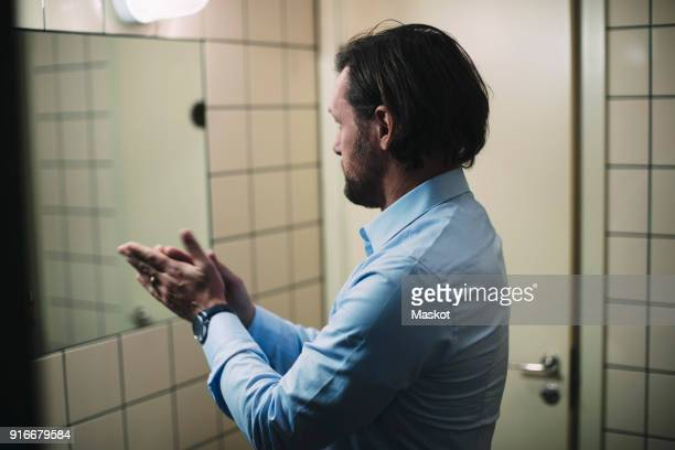 Businessman rubbing hands while standing in front of mirror at bathroom