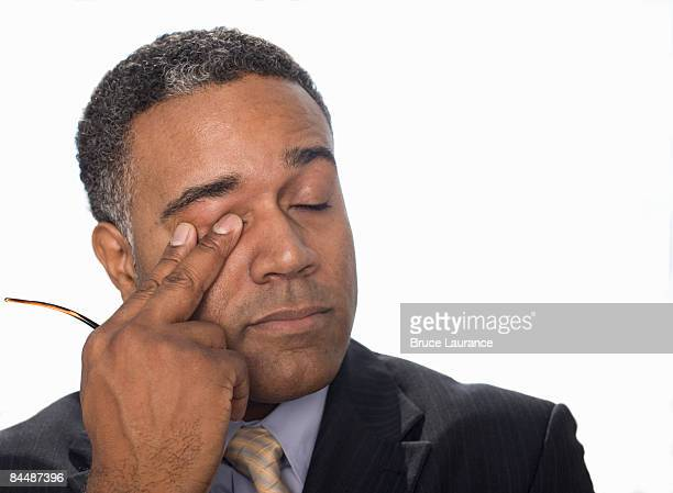 Businessman rubbing his eye
