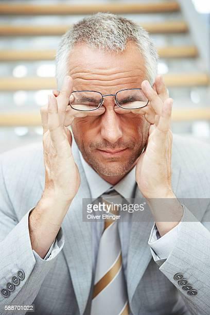 businessman rubbing his eyes - oliver eltinger stock-fotos und bilder