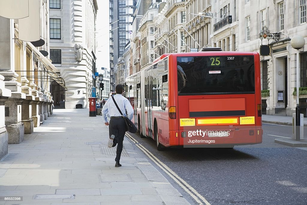 Businessman running after bus in London, England : Stock Photo