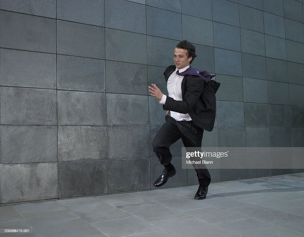 Businessman running against wind : Stock Photo