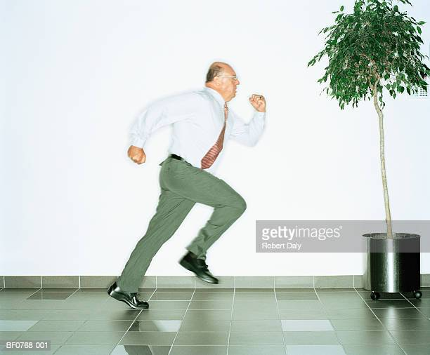 Businessman running along corridor, profile