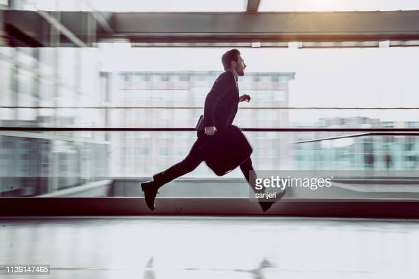 businessman running along the corridor - istantanea foto e immagini stock