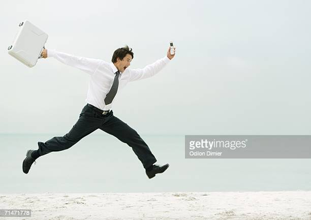 Businessman running and jumping on beach