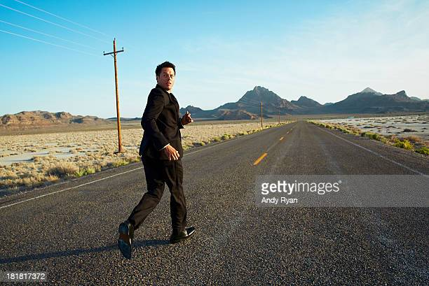 Businessman running down desert road, looking back